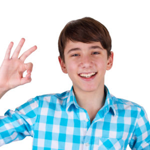 Happy teenager gesturing OK sign and smiling isolated on white background